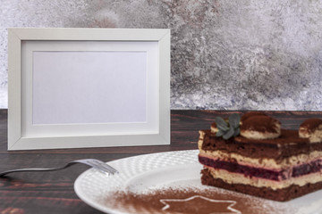 Christmas cake with plum jam and fresh mint on a wooden brown table in front of a concrete wall and a white frame for text