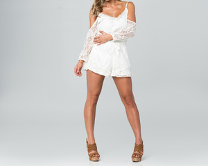 Model in a white shorts romper/playsuit