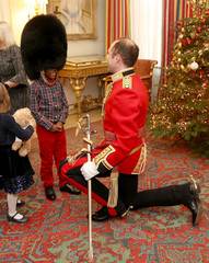A royal guard welcomes a young boy from Helen & Douglas House and Roald Dhal's Marvellous Children's Charity during his visit to Clarence House in London