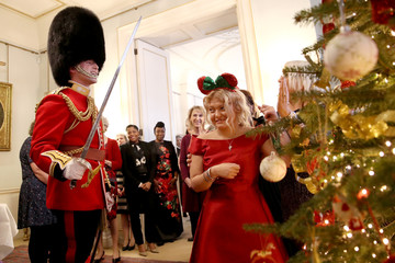 A royal guard welcomes a girl from Helen & Douglas House and Roald Dhal's Marvellous Children's Charity during his visit to Clarence House in London