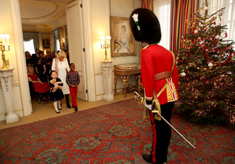 A royal guard welcomes children from Helen & Douglas House and Roald Dhal's Marvellous Children's Charity as they arrive to visit Clarence House with Britain's Camilla, Duchess of Cornwall in London