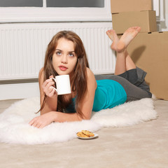 Young woman lying down next to boxes