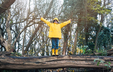 Child with Yellow Rain Boots Playing and exploring outdoors in an Autumn Forest enjoying nature