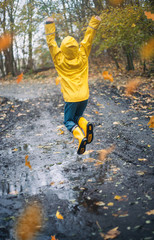 Child with Yellow Rain Boots Playing outdoors in an Autumn Forest jumping in puddles enjoying nature with Falling Leaves
