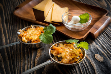 Hot dish of mushrooms, chicken baked in a creamy sauce bechamel, under a cheese crust, green decoration, in small ceramic bowls on a dark background.