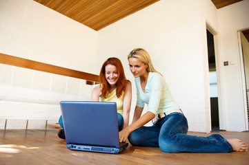 Women using laptop on floor together
