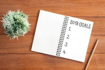 Minimal work space - Creative flat lay photo of workspace desk with 2018 Goal New Year list notebook and wooden pencil on wooden background. Top view flat lay photography. 2018 happy new year concept.