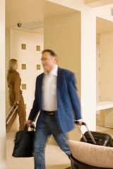 Businessman rolling luggage in walkway