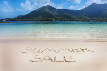 The Summer sale word written on the beach sand.