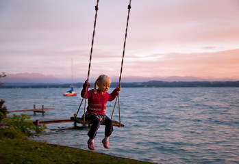 Girl swinging by lake