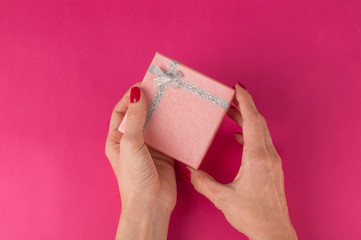 Woman's hand holding a present box on the pink background. St. Valentine's Day
