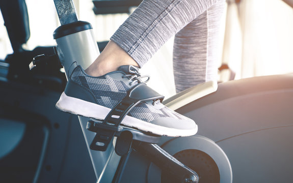 Woman feet is cycling on fitness spinning bike machine