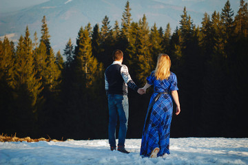 Beautiful young couple over amazingly snowy mountains