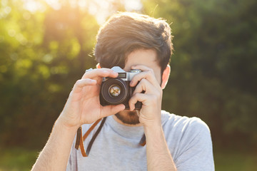 Young male photographer tries retro camera for making photos outdoor, catches beautiful landscapes in objective, enjoys sunlight and nice pictures. Talented amateur professional photographer
