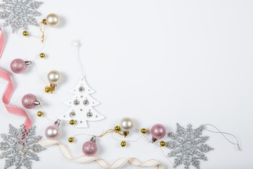 Christmas holiday composition. Festive creative gold silver pattern, xmas pink decor holiday ball with ribbon, snowflakes on white background. Flat lay, top view