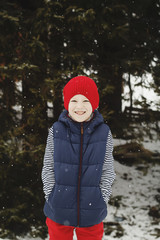 Young happy kid standing on the top of mountain in snowy winter