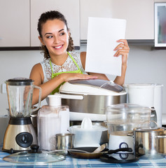 Happy housewife with culinary devices
