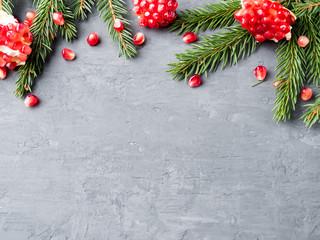 Peeled juicy red garnet in a vintage plate on Christmas tree, selective focus