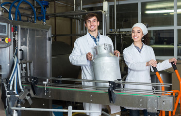 Couple bottling milk on manufacture