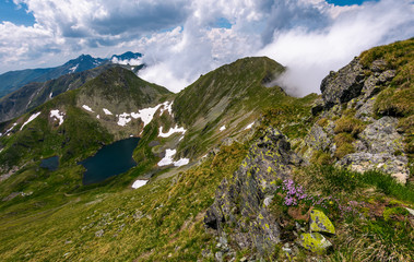 edge of steep slope on rocky hillside in cloudy weather. dramatic scenery with snow near glacier in Fagaras mountains