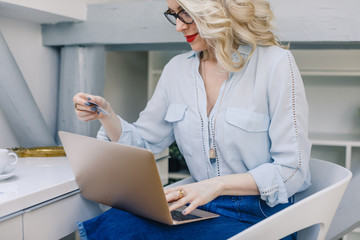 Beautiful Caucasian woman holding credit card for online payment and typing on her laptop.