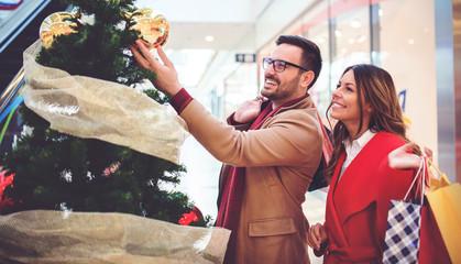 Beautiful young couple looking for Christmas and New Year's presents, having fun together in shopping mall. Consumerism, love, dating, lifestyle concept