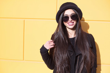 Outdoor fashion portrait of glamour sensual young stylish lady wearing trendy fall outfit , black hat , black coat and stylish sunglasses.