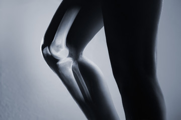 Human knee joint and leg in x-ray, on gray background. The knee joint is highlighted by red colour.