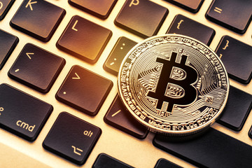 Bitcoin cryptocurrency on laptop keyboard. Close up toned image.