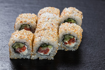 California roll with salmon and cheese arranged on slate plate background