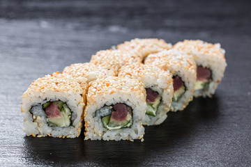 California roll with tuna arranged on slate plate background