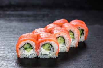 Philadelphia makizushi roll with smoked salmon arranged on stone background