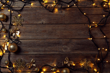 Garland lights with christmas decorations on grey wooden table