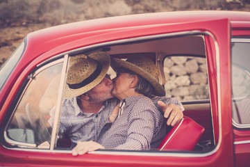 coppia di adulti con cappello che si baciano su un auto rossa vintage . kiss and love for adult caucasian people