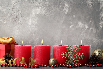 Christmas candles with baubles and gift box on wooden table