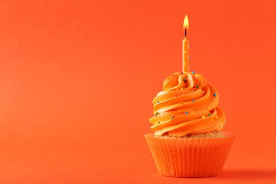 Tasty cupcake with candle on orange background