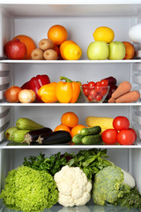 Open fridge full of vegetables and fruits