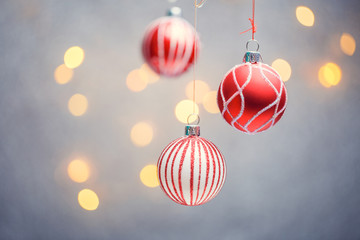 Photo of three Christmas tree red balls with pattern on gray background with hot lights.