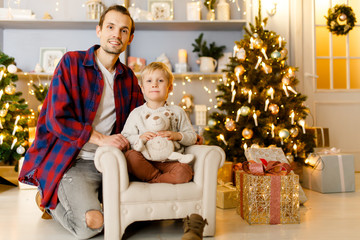 New Year's photo of father hugging son sitting on armchair