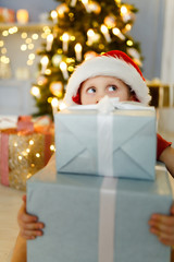 New Year's image of boy in santa hat with gift box on background