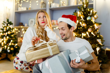 Image of cheerful couple in Santa cap with gift in box