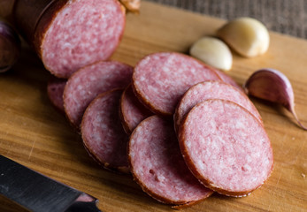 Slices of sausage and garlic lie cutting board