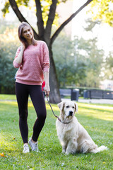 Photo of brunette holding leash of labrador on lawn