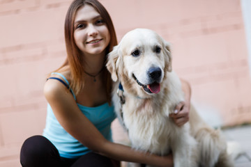 Image of fitness brunette hugging labrador near building wall