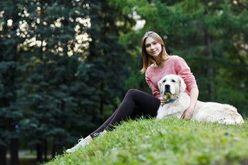 Image from below of girl sitting with dog on green lawn
