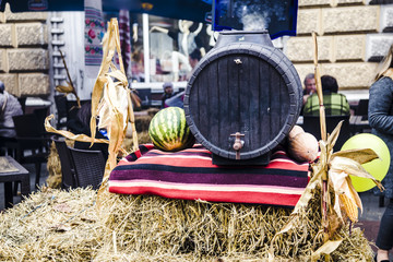 Moldovan national holiday, oak wine barrel on the hay, next to watermelon, pumpkin and corn