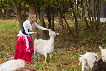 Glad woman stroking goats on a green glade