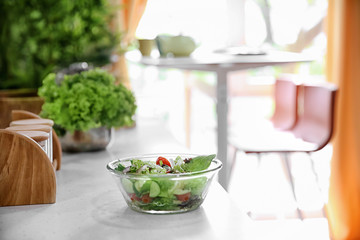 Bowl with tasty vegetable salad in modern kitchen