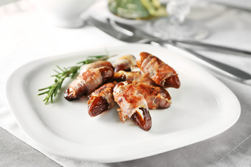 Plate with bacon wrapped dates on table