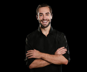 Young handsome man smiling on black background
